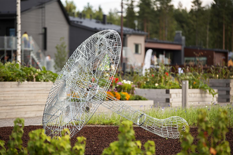 Teräslangasta taivutettu sienimäinen taideteos, joka on sijoitettu puistoon.