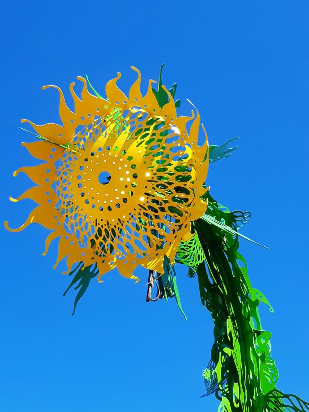 Auringonkukkaa muistuttava 8 metriä korkea teräsveistos. Taiteilija Pekka Jylhän teos.