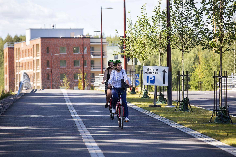 Polkupyöräilijät Rykmentinpuistossa. Taustalla A-Kruunun rakennuttama punatiilinen kerrostalo.